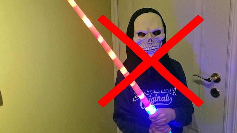 barn utklädd med ansiktsmask och lasersvärd i plast, rött kryss över bilden Halloween