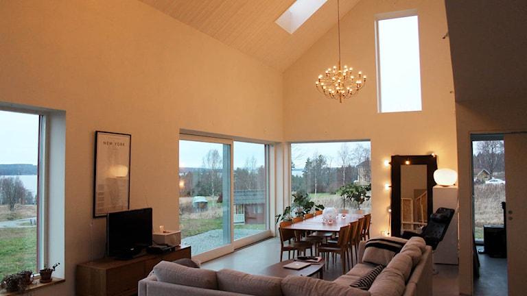 Bild innifrån huset, med öppen planlösning med stora fönster.