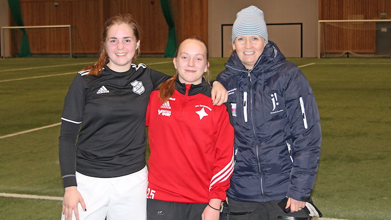 Två fotbollsspelande tjejer tillsammans med en tränare i träningsanläggningen ÖP-hallen i Östersund.