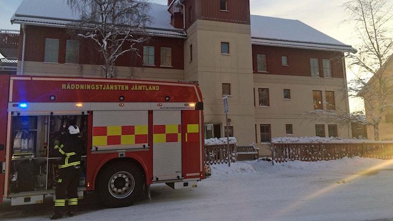 Bild på ett flerfamiljshus som det står en brandbil utanför. En brandman syns vid brandbilen.