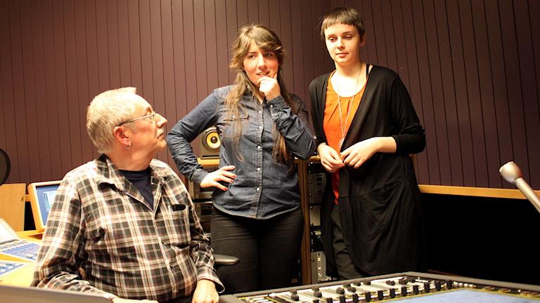 en man i rutig skjorta och två unga kvinnor står i teknikstuduio på radio