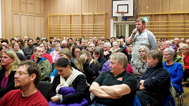 Många besökare samlade i en gymnastiksal i Hallen där det hölls ett skolmöte. En man står upp och ställer en fråga.