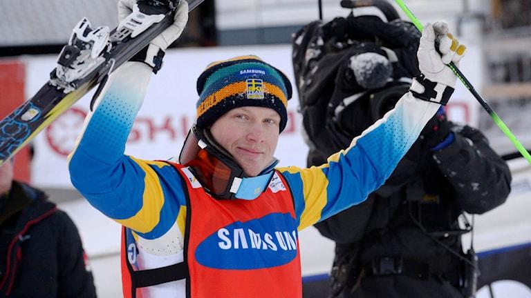 Victor Öhling Norberg höjer händer mot luften med skida och stav i händerna