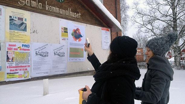 Sara Norling och Sol Vikström från Länskulturen sätter upp affischer om kulturbussen Filmrullen som börjar rulla runt på länets vägar i mitten av mars.  Foto: Ann-Louise Rönestål Ek.