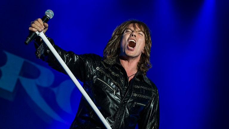Sångaren Joey Tempest i Europe med mikrofonstativ på scen