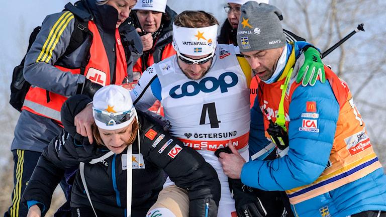 Sveriges Emil Jönsson tas omhand av bland annat Rikard Grip (t h) efter skada under sprintkvartsfinalen (k) vid lördagens världscuptävling i Östersund. Foto: Henrik Montgomery / TT