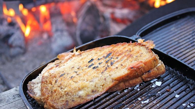 Grillad macka i smörgåsjärn vid eldstad