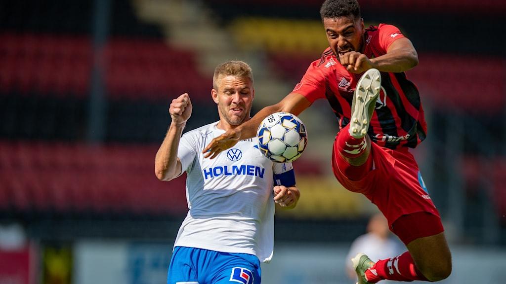 Två manliga fotbollsspelare i kamp om bollen där den ene hoppar och sparkar mot bollen