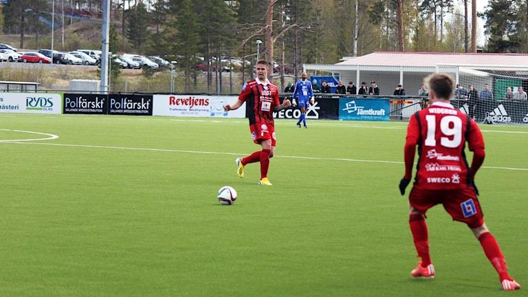 Douglas Bergqvist passar fotbollen till Dennis Widgren