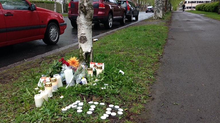 Blommor och ljus på platsen där en 23-åring knivhöggs till döds tidigt på nationaldagens morgon. 150606. Foto: Pernilla Anth Jacobsson/SR