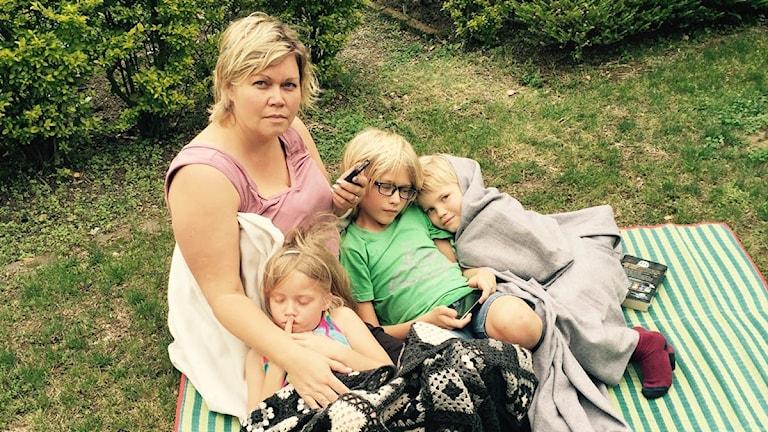 Mirjam Thiessen sitter på en filt med sina tre vbarn
