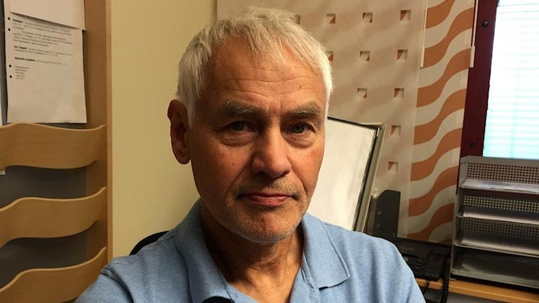En man sitter vid ett skrivbord och tittar in i kameran.
