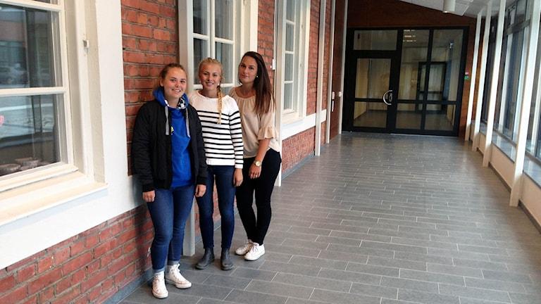 Tre tjejer står i en kolkorridor