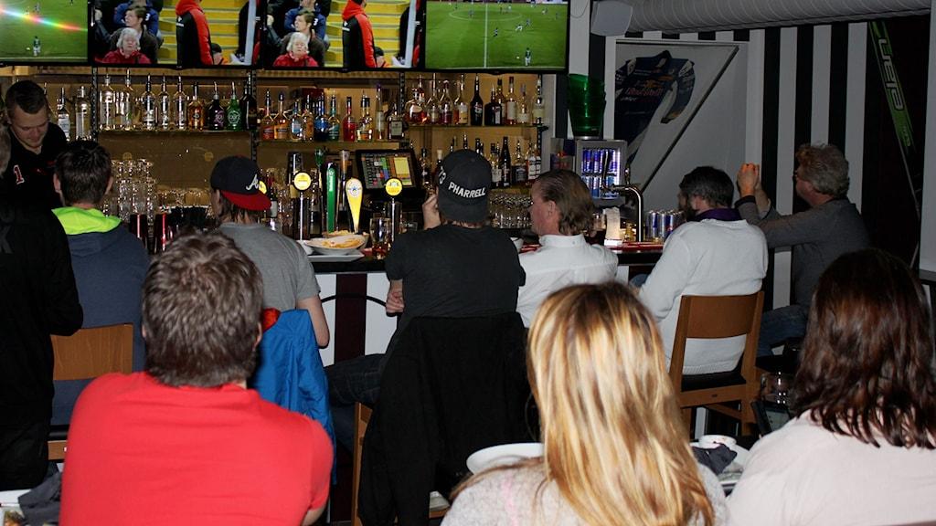 Folk ser fotboll på restaurang.