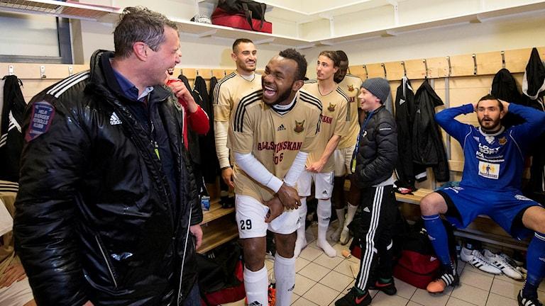 Daniel Kindberg och spelaren Michael Omoh firar i omklädningsrummet