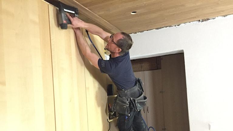 Hantverkare står på stege och bygger innertak.