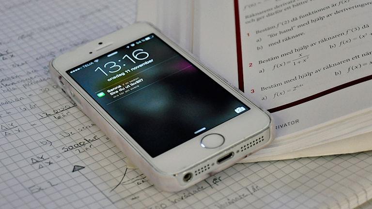 Mobiltelefon ligger i mattebok. Foto: JGY.