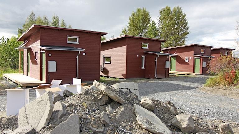 Hög med grus och betong framför rödmålade små trähus