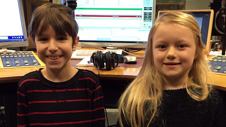 En pojke och en flicka står i en radiostudio.
