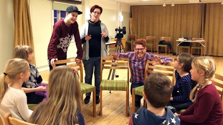 Barn sitter på stolar i en ring och har audition på Jamtli.