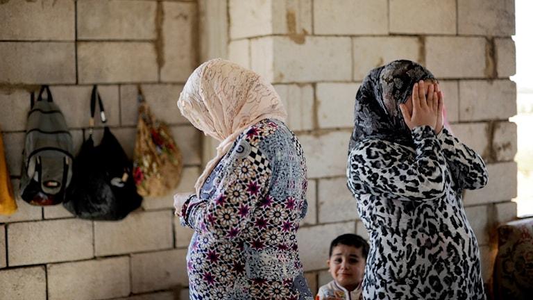 Två kvinnor och ett barn ser förtvivlade ut. De befinner sig inne i en kal byggnad.