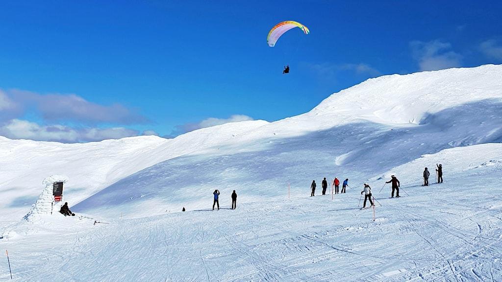 En bild på en skidbacke i strålande sol med en skrämflygare på himlen och skidåkare i backen