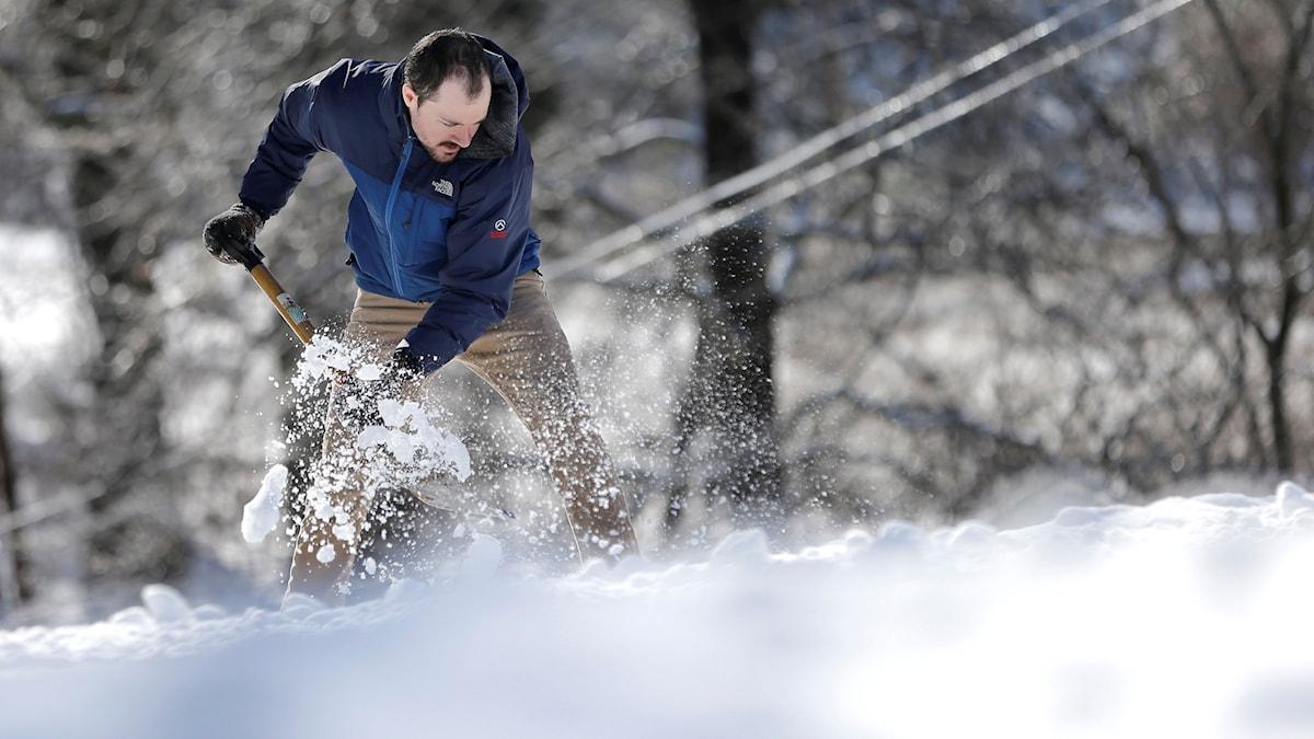 Man som skottar snö. Foto: Mark Humphrey/AP
