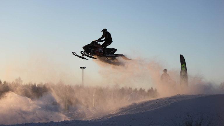 Skoterförare hoppar över en kulle