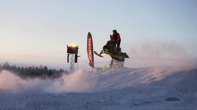 Skoterförare som hoppar över en kulle