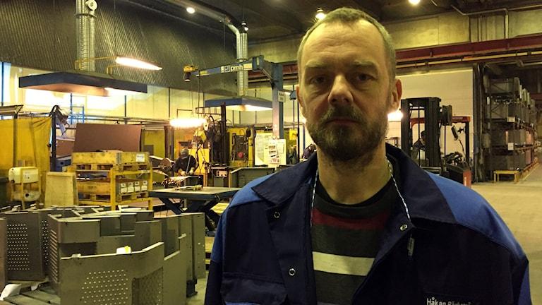 En man står i en fabrik och tittar in i kameran.