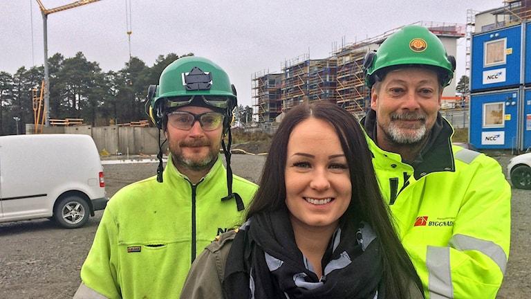 en kvinna står framför två byggnadsarbetare
