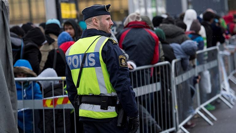 En polis övervakar kön av ankommande flyktingar vid Hyllie station utanför Malmö.