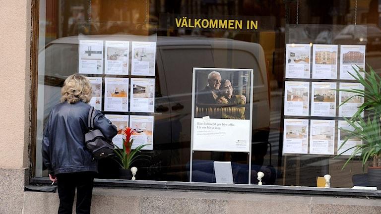 Kvinna tittar i skyltfönster hos bostadsmäklare