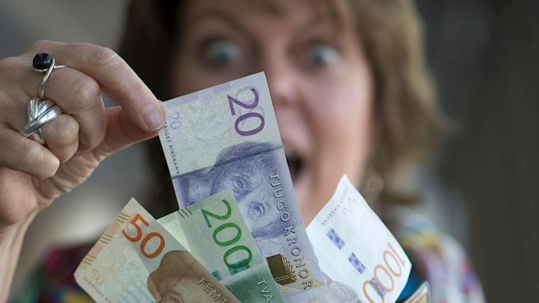 STOCKHOLM 201510 Glad kvinna med plånbok och de nya svenska sedlarna. Foto: Fredrik Sandberg / TT / Kod 10080