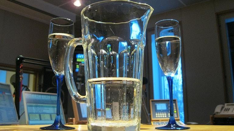Vatten i karaff och höga glas i radiostudio