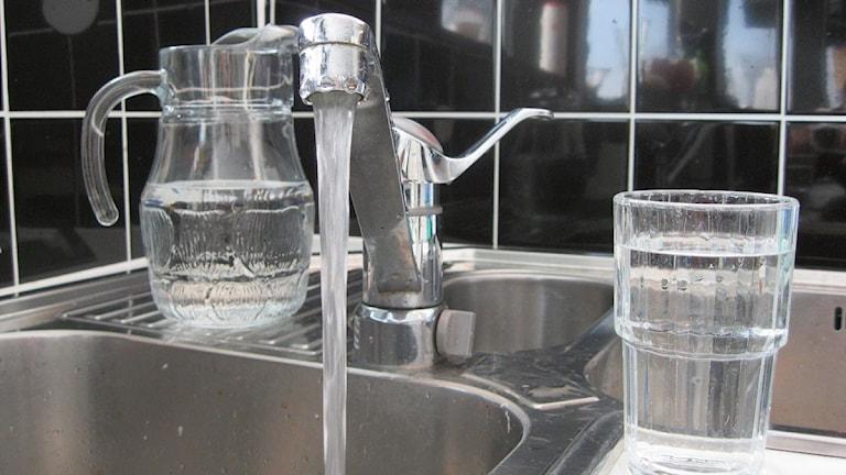 Diskho med vatten rinnande ur vattenkran, vattenkaraff och vattenglas
