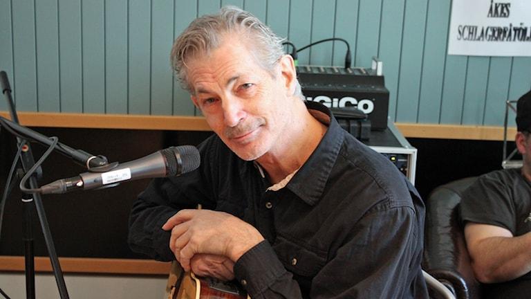 Doug Seagers sitter med sin gitarr vid mikrofonen.