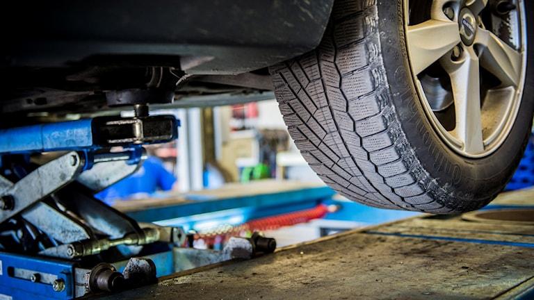 Underredet till en bil är upphissad med en domkraft på en bilverkstad.