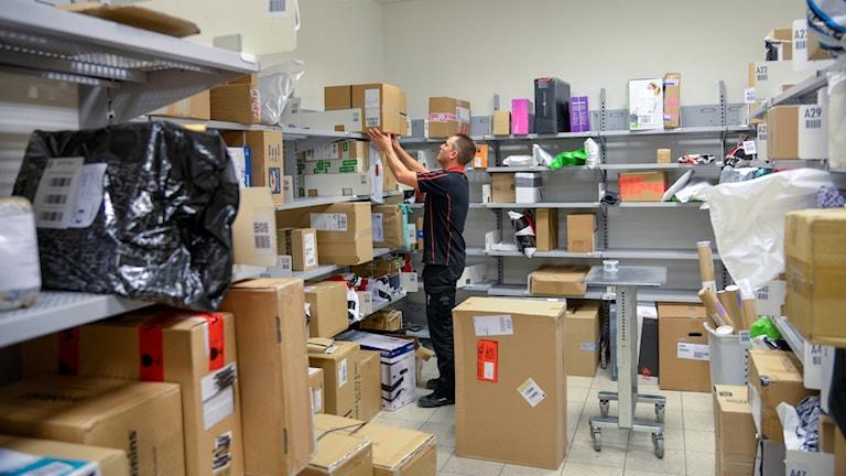 En man i en mataffär sorterar postpaket.