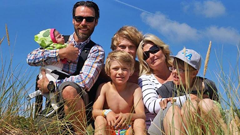 Familjebild - två vuxna och fyra barn sitter tillsammans under blå himmel.