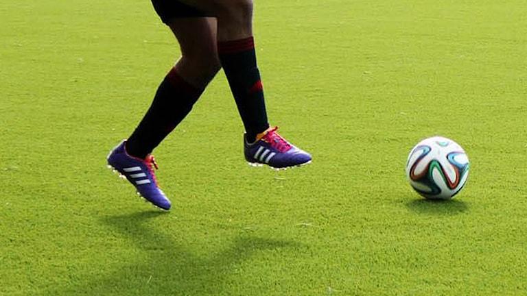 Fotbollspelares ben och en fotboll på konstgräs (ÖFK-spelare)