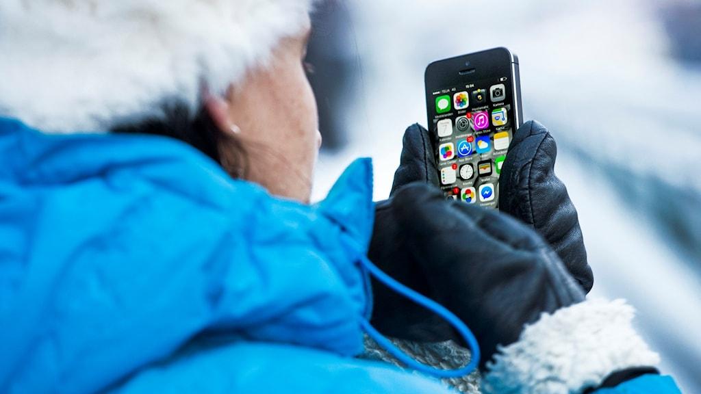 Vinterklädd person håller i mobiltelefon