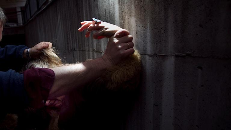 Man trycker upp kvinna mot vägg utomhus
