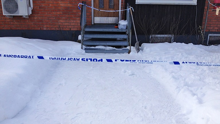 Vy framför ett hus med polisavspärrning.