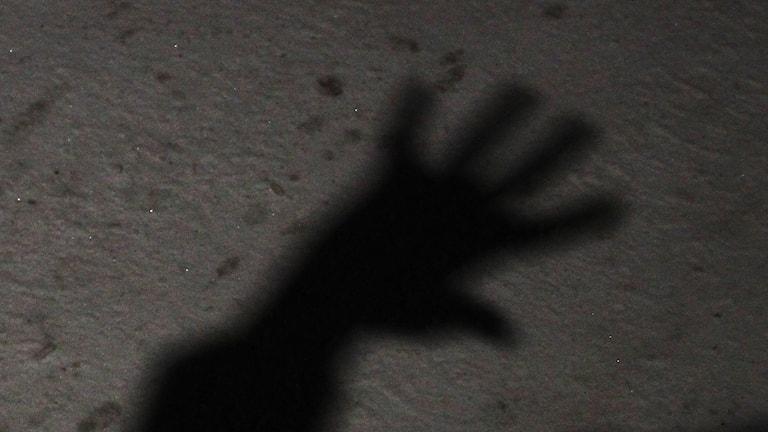 Skuggan av en uppsträckt hand.