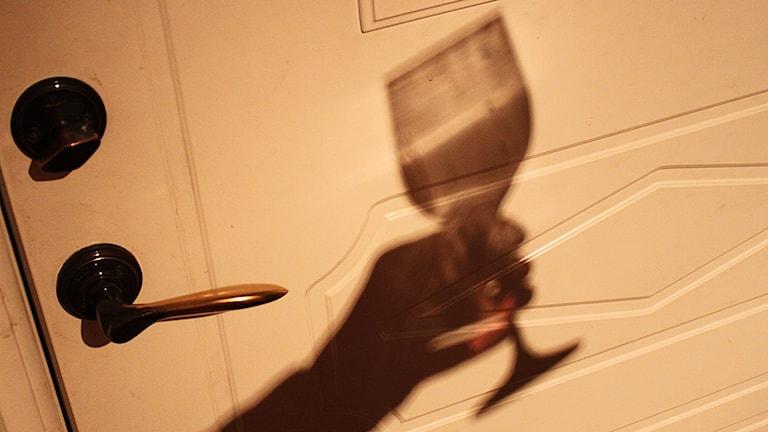 Skuggan av kvinnohand med tomt vinglas vid ytterdörr