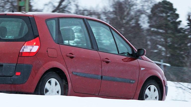 Röd personbil på vinterväg