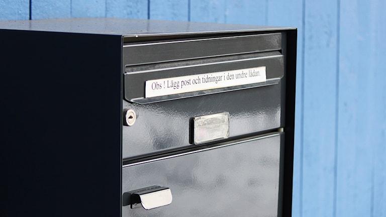 Svart postlåda på husvägg