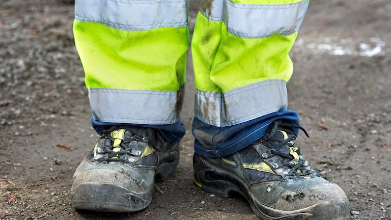 Fötterna på en person som har arbetsskor och reflesxbyxor.