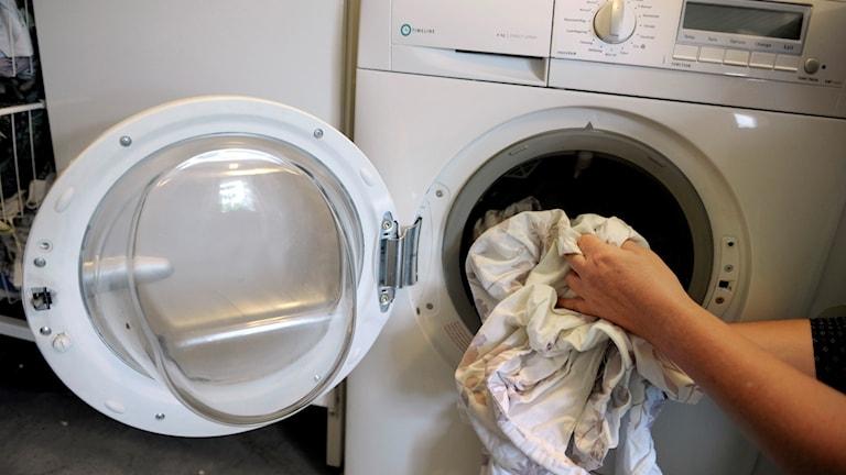Någon stoppar in kläder i en tvättmaskin.